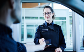Photo of a BSO giving back a passport to a traveller - Photo d'une ASF redonnant un passeport à un voyageur